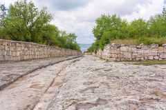 Borggården av den forntida grottastaden av Chufut grönkål, brutet spår från hjulen av forntida medel, Arba, vagn, vagn arkivbilder