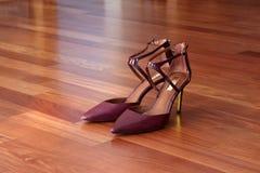 Borgogna alla moda ha tallonato le scarpe su un pavimento di legno duro Fotografia Stock Libera da Diritti