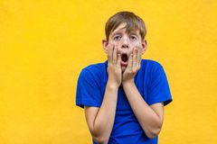 So boring. Alone sad boy looking and camera with open mouth. Stock Photo