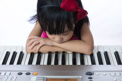 Boring Asian Chinese little girl playing electric piano keyboard Stock Image