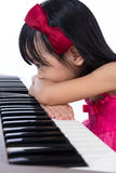 Boring Asian Chinese little girl playing electric piano keyboard. In the living room at home royalty free stock photography