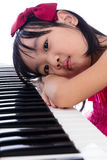 Boring Asian Chinese little girl playing electric piano keyboard Royalty Free Stock Image