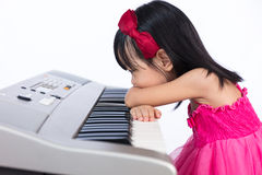 Boring Asian Chinese little girl playing electric piano keyboard Stock Photography