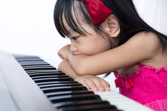 Boring Asian Chinese little girl playing electric piano keyboard Stock Images