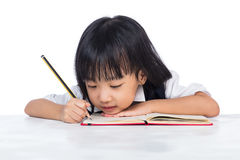 Boring Asian Chinese little girl wearing school uniform studying Stock Image