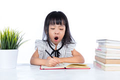 Boring Asian Chinese little office lady writing book. In isolated white background royalty free stock images
