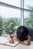 Boring asian little Chinese girl writing homework Stock Photos