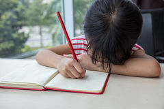 Boring asian little Chinese girl writing homework Stock Photos