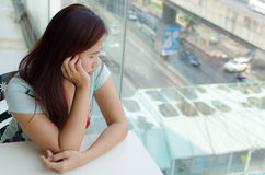 Boring Asian woman. Side profile of Asian woman who is looking outside window Stock Images