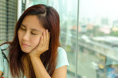Boring Asian woman. Asian woman who is closing eyes and putting hand on her chin, photographed next to skyscraper window Royalty Free Stock Photography