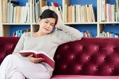 Boring book. Pretty mature woman reading boring book at home royalty free stock photography