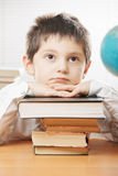 Boring boy leaning on stack of books Royalty Free Stock Images