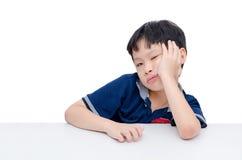Boring boy sitting over white Stock Images