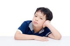 Boring boy sitting over white. Boring Asian boy sitting over white background royalty free stock images