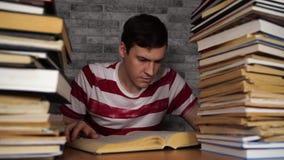 Boring de lezingsboek van de mensenstudent bij bibliotheek met heel wat boeken op universiteit Ontmoedigde student het lezen van  stock videobeelden