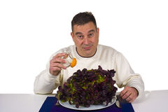 Boring diet. Pouring salt on a boring, raw lettuce, diet concept Stock Photo