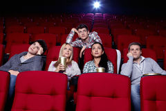Boring film. Satisfied girls and bored boys watching a movie at the cinema Stock Photo