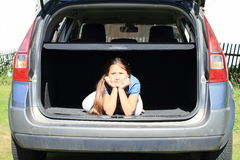 Boring girl in car trunk Stock Photo