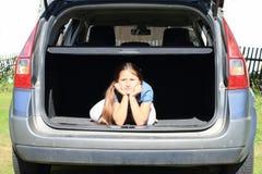Boring girl in car trunk Stock Photo