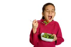 Boring healthy food. A young girl yawning showing boredom at having to eat her bowl of fresh salad, isolated on white. Concept : Healthy eating Royalty Free Stock Photography