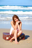Boring holidays. A beautiful Caucasian white young woman model with sad facial expression sitting on her big brown suitcase on the beach without money in her Stock Photo