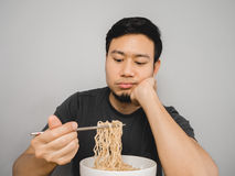 Boring instant noodles. Poor Asian man feel boring with the same old instant noodle royalty free stock photography