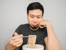 Boring instant noodles. Poor Asian man feel boring with the same old instant noodle royalty free stock images