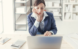 Boring job. Depressed bored businesswoman working at office desk and networking with a laptop, boring job concept stock photos
