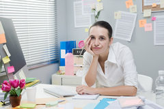 Boring job. Tired frustrated female office worker at desk looking at camera stock images