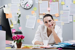 Boring job. Tired frustrated female office worker at desk looking at camera royalty free stock photography