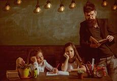 Boring lessenconcept Leraar en meisjesleerlingen in klaslokaal, bord op achtergrond De mens met baard onderwijst stock afbeeldingen