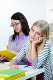 Boring lesson. Portrait of pensive teenage blonde listening to the teacher reading book at lesson stock photos
