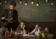 Boring lesson concept. Teacher and girls pupils in classroom, chalkboard on background. Man with beard teaches. Schoolgirls, reading book. Bored and tired royalty free stock photos