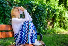 Boring literature. Woman tired face blonde take break relaxing in garden reading book. Lady student read boring. Literature outdoors. Girl sit bench relaxing stock photo
