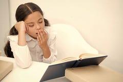 Boring literatuur Het meisjeskind leest boek terwijl lijst witte achtergrond zit Schoolmeisje die en boek bestuderen lezen kid stock foto's