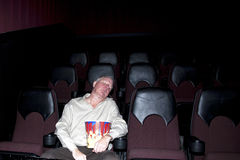 Boring Movie. Senior man in an empty movie theater asleep in his seat with a bowl of popcorn in his lap Stock Image
