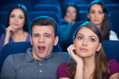Boring movie?. Bored young men sitting close to his excited women while watching movie at the cinema Royalty Free Stock Photos