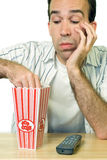 Boring Movie. A man eating popcorn while watching a boring movie Royalty Free Stock Photos