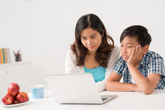 Boring movie. Bored child watching something on laptop with his mother Stock Photo