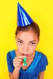 Boring new years party woman. Funny sad party woman in blue on yellow background. Beautiful mixed race / asian caucasian model with party hat blowing a party Royalty Free Stock Photography