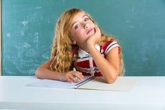Boring sad expression student schoolgirl on desk Stock Image