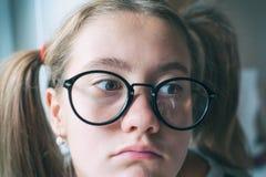 Boring School Nerdy grappig meisje met paardestaarten in oogglazen stock afbeelding