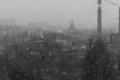 Boring, sombere zwart-witte cityscape met sneeuw, bomen, huizen en een kerk en een fabrieksschoorsteen Dit is Rusland stock foto