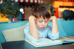 Boring and tired little boy reading book. For elementary school Stock Image