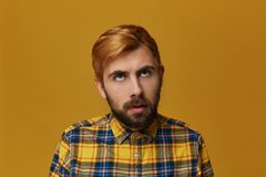 Boring to death! Young bearded male, wearing yellow t-shirt, dyed hair feels bored and thinkin about home. Isolated over yellow studio background Stock Images