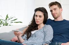 Boring tv program. Bored young couple watching television at home Royalty Free Stock Photo