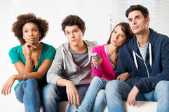 Boring tv programs. Group Of Young Friends Watching Television with bored expressions Stock Images