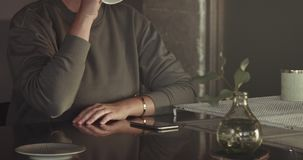 Boring unrecognizible woman using mobile phone during tea time stock footage