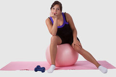Boring workout. Young brunette aboriginal teen girl wearing workout attire sitting on big pink ball looking bored stock images