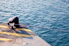 Borne dans le port avec la corde faite une boucle autour Image libre de droits